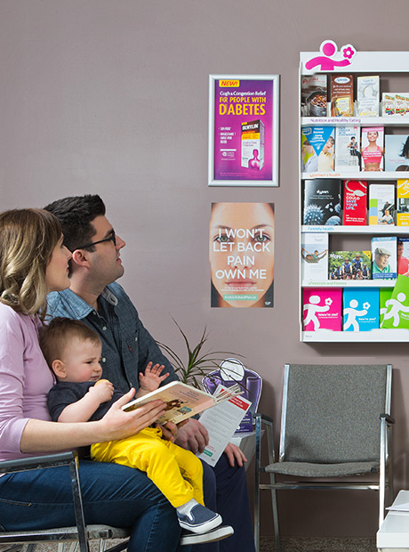 A young couple with child looking at an IDS brochure display in waiting room